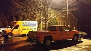 Water Damage Restoration Trucks Parked At Residential Job Site At Night